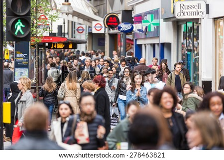 LONDON, UNITED KINGDOM - APRIL 17, 2015: Crowded sidewalk on Oxford Street with commuters and tourists from all over the world. - stock photo