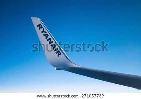 LONDON, UNITED KINGDOM - April 12, 2015: Ryanair logo on airplane's wing in mid-air over United Kingdom