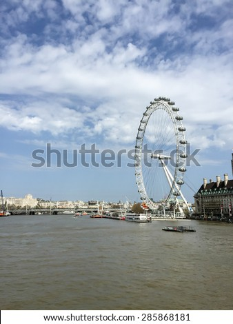 LONDON, UNITED KINGDOM - APRIL 16, 2015: The famous Ferris wheel, London eye near river Thames with blue sky. London is the world's most-visited city as measured by international arrivals. - stock photo