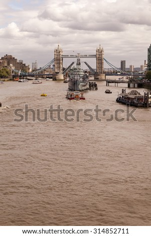 London, United Kingdom - August 04, 2015: Decommissioned battleship HMS Belfast in River Thames moored between London Bridge City Pier and one of Britains most famous landmarks, The Tower Bridge.  - stock photo