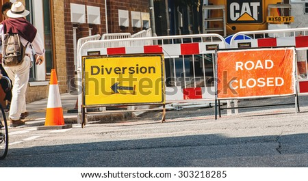 LONDON, UNITED KINGDOM - AUGUST 28, 2013: Road closed sign and diversion on London streets during reconstruction with pedestrian walking and tractor working - stock photo