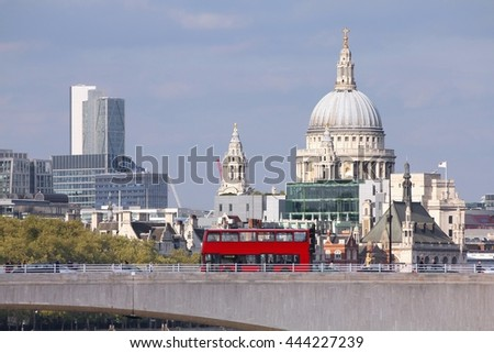 London, United Kingdom - cityscape with famous St. Paul's Cathedral and a bridge with red doubledecker bus - stock photo