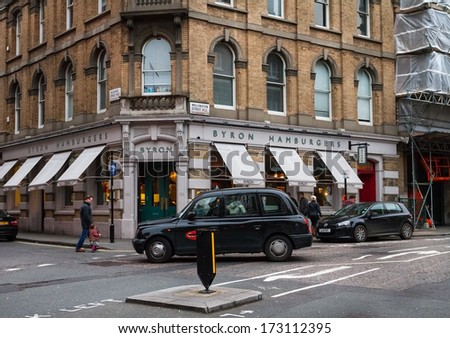 LONDON, UNITED KINGDOM - DECEMBER 27, 2011: Taxi passing by the Byron Hamburgers, very popular restaurant chain specialised in hamburgers. - stock photo