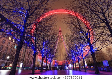 LONDON, UNITED KINGDOM -?? 24 JANUARY 2016: Long exposure of London Eye with red light and blue lighting decoration on trees. At a height of 135m, it is the tallest Ferris wheel in Europe. - stock photo