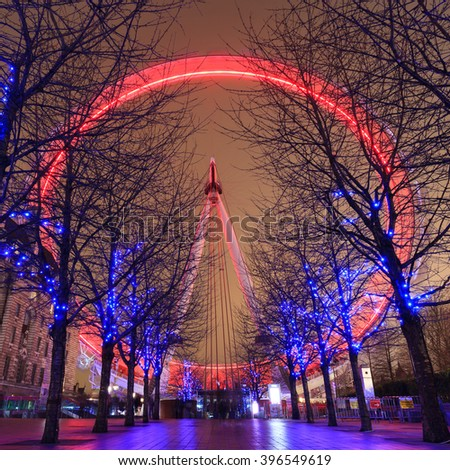 LONDON, UNITED KINGDOM -? 24 JANUARY 2016: Long exposure of London Eye with red light and blue lighting decoration on trees. At a height of 135m, it is the tallest Ferris wheel in Europe. - stock photo