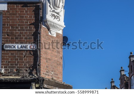 LONDON, UNITED KINGDOM - JANUARY 17, 2017: Sign for Brick Lane in Borough of Tower Hamlets with blue sky and roof tops. The street is well known for its curry houses.