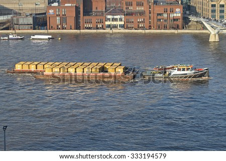 LONDON, UNITED KINGDOM - JANUARY 21, 2011: Tugboat and Container Barge at Thames River. Shipping Municipal Garbage To Waste Management Facility, London, England. - stock photo