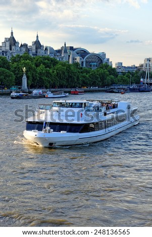 LONDON, UNITED KINGDOM - JULY 1, 2014: A City Cruises tour boat sails on the Thames River near Westminster. Thames is the longest river in England with 346 km in length. - stock photo
