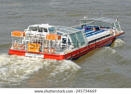LONDON, UNITED KINGDOM - JULY 1, 2014: A City Cruises tour boat sails on the Thames River. Thames is the longest river in England with 346 km (215 miles) long. - stock photo