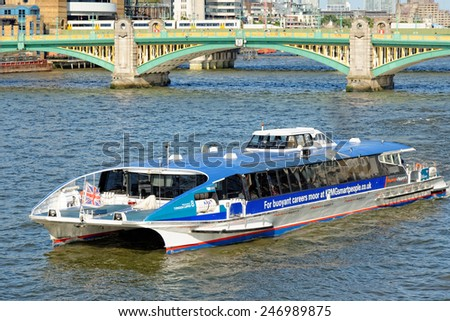 LONDON, UNITED KINGDOM - JULY 1, 2014: A City Cruises tour boat sails on the Thames River, with Southwark bridge in the background. Thames is the longest river in England with 346 km in length. - stock photo