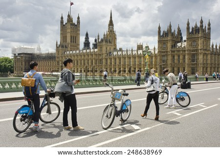 LONDON, UNITED KINGDOM - JULY 7: tourists on Westminster Bridge on July 7, 2014 in London, United Kingdom. Westminster Bridge is a road and foot traffic bridge over the River Thames in London. - stock photo