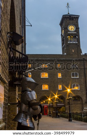 London, United Kingdom - March 23, 2016: Street view of the Medieval Tower, with a suit of armour and a red telephone cabin near the clocktower in London, United Kingdom, on the 23rd of March 2016. - stock photo