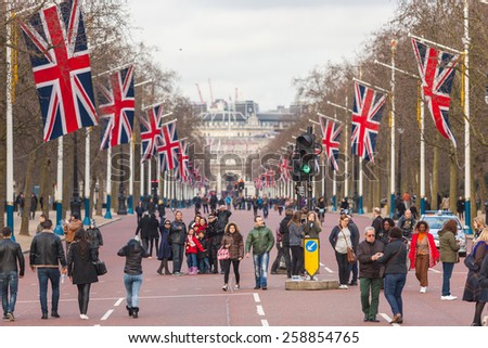 LONDON, UNITED KINGDOM - MARCH 8, 2015: The Mall road with many big United Kingdom flags, also known as Union Jack. Some tourists are walking on the street. - stock photo