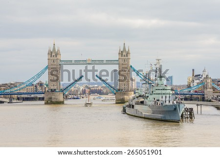 LONDON, UNITED KINGDOM - MARCH 22, 2015: Tower bridge opening on a cloudy day and HMS Belfast in the foreground. London, England, United Kingdom