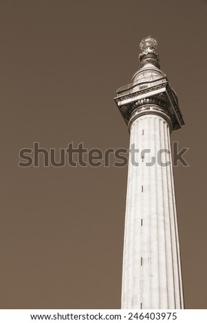 London, United Kingdom - Monument to the Great Fire of London. Sepia tone - filtered retro style monochrome photo. - stock photo