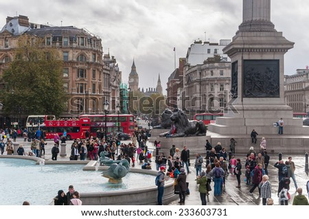 LONDON, UNITED KINGDOM - NOVEMBER 8, 2014: Tourists visit Trafalgar Square on a cloudy day. It is one of the most popular tourist attraction in London, often considered the heart of London. - stock photo