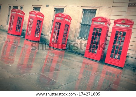 London, United Kingdom - red telephone boxes in wet rainy weather. View of Broad Court, Covent Garden. - stock photo