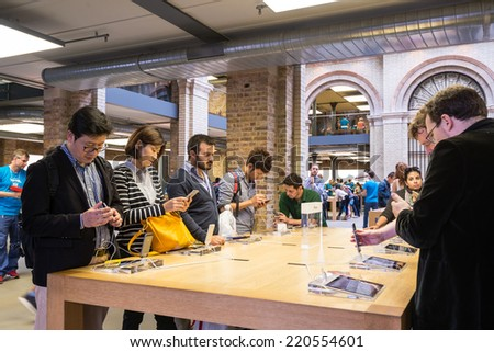 London, United Kingdom - SEPTEMBER 26, 2014: Customers admiring the new Apple iPhone 6 and iPhone 6 Plus at the Apple Inc. store on September 26, 2014 in Covent Garden in London, UK. - stock photo
