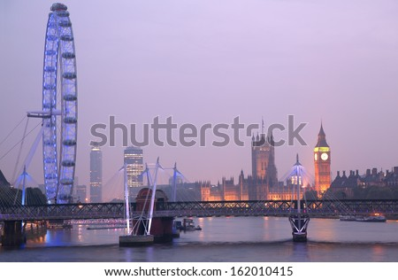 LONDON, UNITED KINGDOM - SEPTEMBER 24: London Eye at dusk on September 24, 2013 in London, United Kingdom is the tallest Ferris wheel in Europe at 135 meters. Houses of Parliament on the background. - stock photo