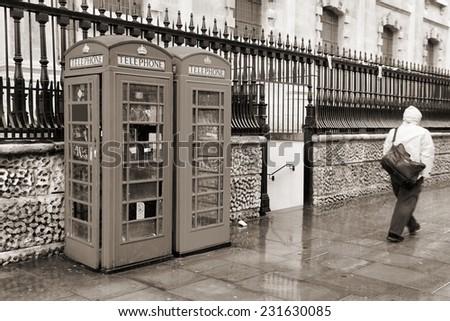 London, United Kingdom - telephone boxes in wet rainy weather. Sepia tone - filtered retro style monochrome photo. - stock photo
