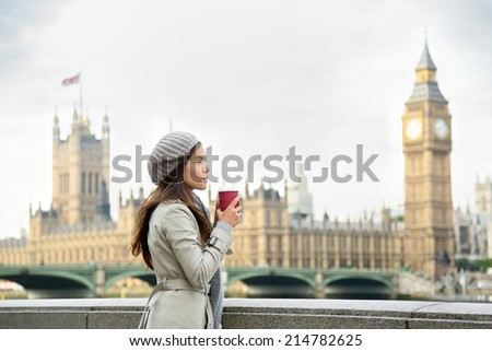 London woman drinking coffee by Westminster Bridge. Serious pensive thoughtful young female professional business woman in London, England. Beautiful young multiracial Asian Caucasian girl. - stock photo