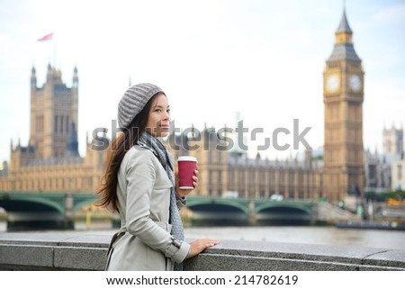 London woman drinking coffee by Westminster Bridge. Young female professional business woman in London, England. Beautiful young multiracial Asian Caucasian girl. - stock photo