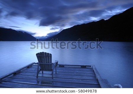 Lone adirondack chairs on a deck  at sunset - stock photo