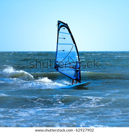 Lone anonymous windsurfer in the ocean catching a wave - stock photo