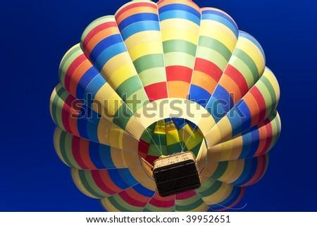 Lone balloon in a blue sky seen from below. - stock photo