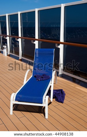 Lone blue deck chair and two bath towels on cruise ship. - stock photo