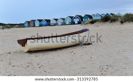 Lone boat on the beach in front of beach huts on the beautiful Dorset coast  - stock photo