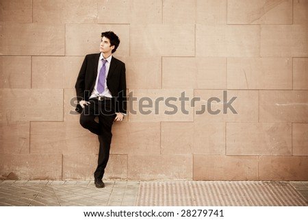Lone businessman posing on wall - stock photo