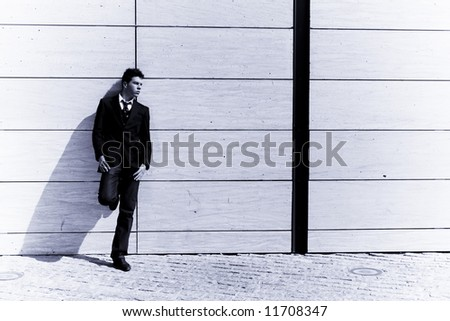 Lone businessman posing on wall, blue toned. - stock photo