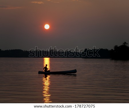 Lone Canoe Sunset Silhouette in Lake - stock photo