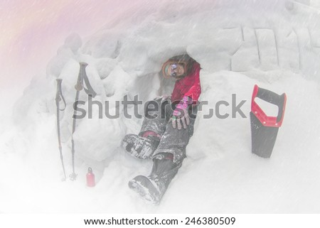 lone climber preparing to spending the night in harsh weather conditions on the background of winter high mountains among the alpine steep slopes and sharp ridges. Security against wind and avalanches - stock photo