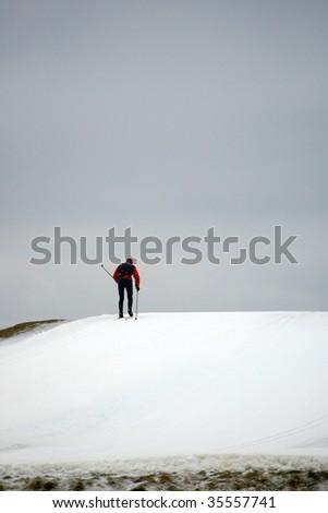 lone cross-country skier climbing uphill - stock photo