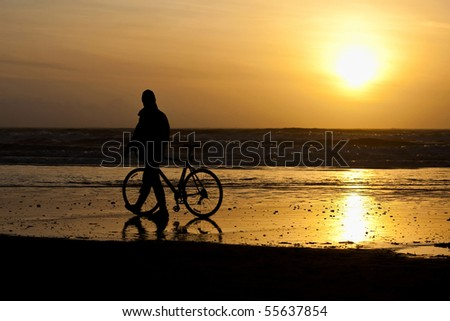 Lone cyclist admires the setting sun - stock photo