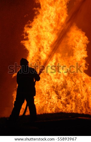 lone fireman battling against raging fire, NOTE: shallow focus on material burning in fire, top left corner particles from water spray, not camera noise - stock photo