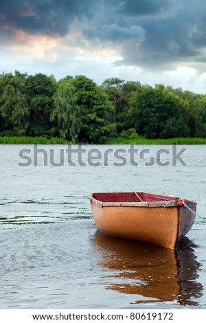 Lone fishing boat floating on the lake - stock photo