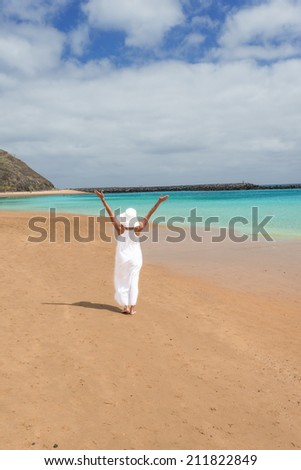 Lone girl in white dress and hat standing on beach - stock photo
