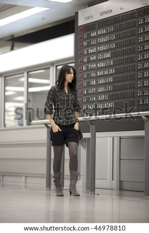 Lone girl waiting at the airport and looking at the scheduled arrivals board. Some noise visible