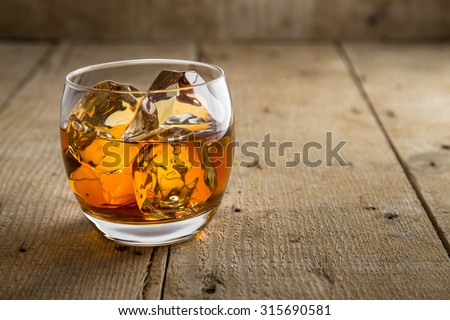 Lone glass of whisky bourbon on the rocks ice vintage reclaimed wood solo wooden liquor whiskey