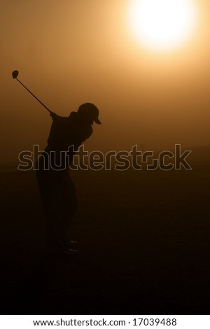 Lone golfer stands in golden morning sunlight