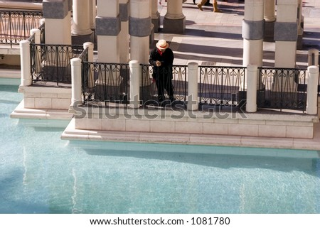 Lone Gondolier Looking At the Water by the Dock - stock photo