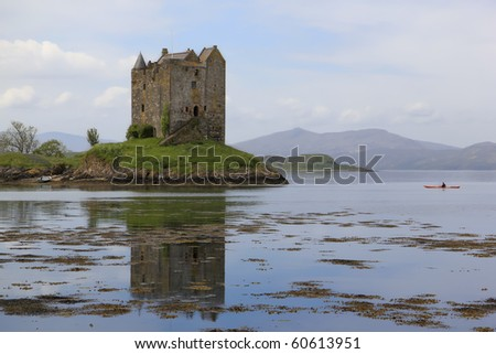 lone kayaker in sea canoe explores  medieval castle stalker on small island in loch linnhe argyll in the scottish highlands - stock photo