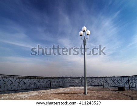 lone lantern on the waterfront against the blue sky - stock photo