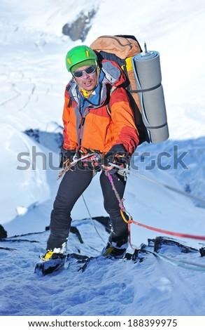 Lone male mountain climber climbing a snowy ridge - stock photo