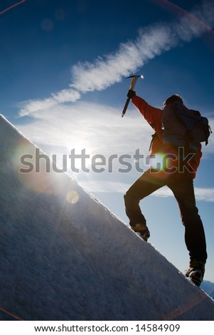 Lone male mountain climber climbing a snowy ridge; Mont Blanc, Europe.