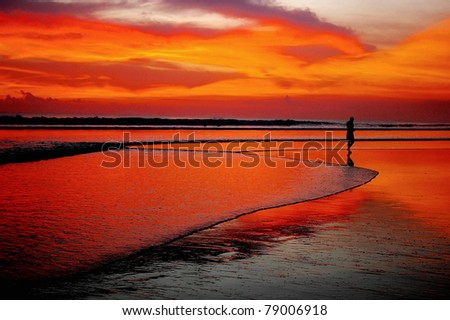 Lone man at sunset on beach, Seminyak, Bali, Indonesia.