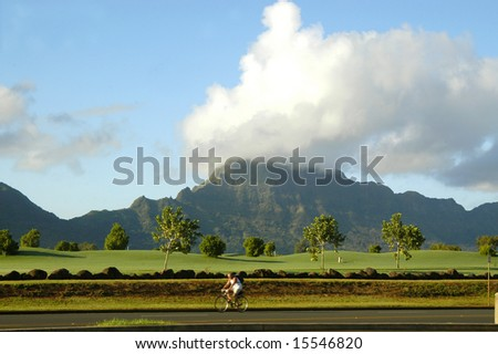 Lone man on bicycle pedals by golf course on Kauai, Hawaii.  Mountains and blue sky in background. - stock photo